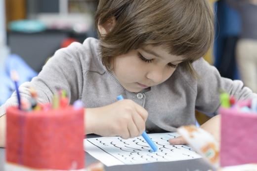 Egy kislány hullámokat rajzol egy papírra.