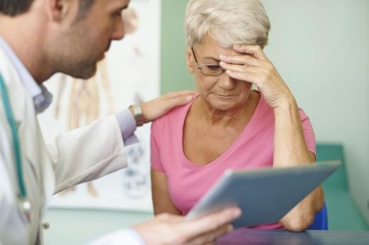 Az orvos, vigasztalva, táblagépen mutatja egy idős nőnek milyen ellátásra jogosult.