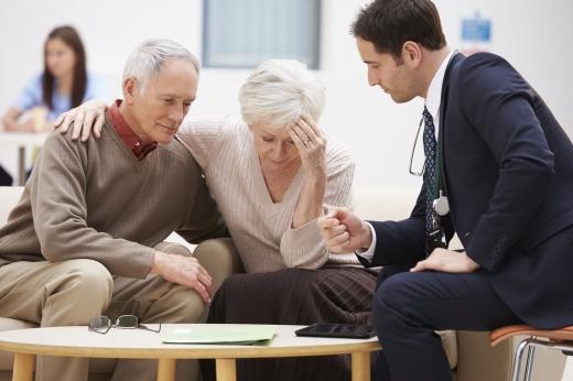 Öltönyös ember tanácsot ad egy idős házaspárnak egy asztalnál ülve.
