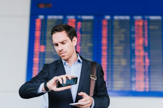 Férfi az óráját nézve, telefonnal a kezében várja a repülőgépét a reptéren.