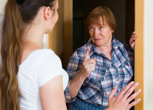 Egy fiatal és egy középkorú nő, a lakás ajtajában fenyegetőzve vitatkozik.