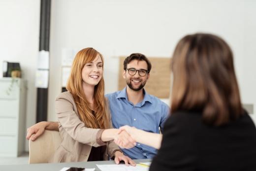 Fiatal házaspár kezet fog egy biztosító munkatársával a sikeres biztosítás megkötése után.