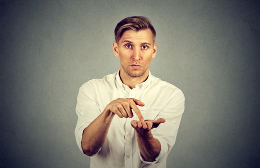Egy férfi mérgesen és kérdően mutat a tenyerébe, a bérét követelve.
