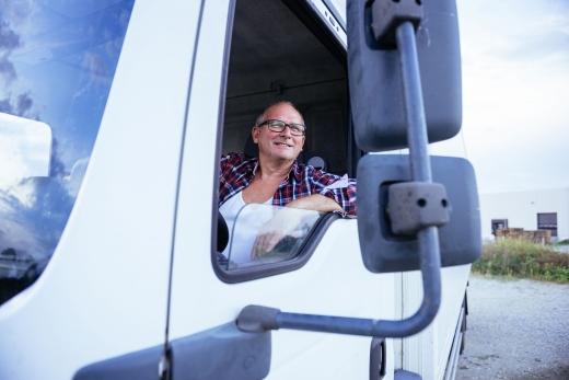 Egy teher autó söforje vidám tölti pihenőidejét az autóban ülve.
