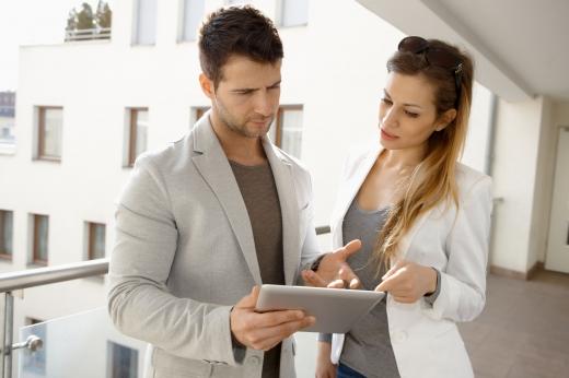 Egy féri és egy nő, a táblagépét nézegeti egy társasház folyosóján.