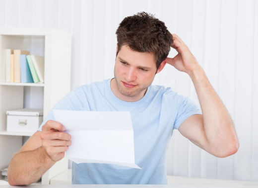 Fiatal férfi vakarja a tarkóját gondterhelten, miközben egy fizetési meghagyást olvas.