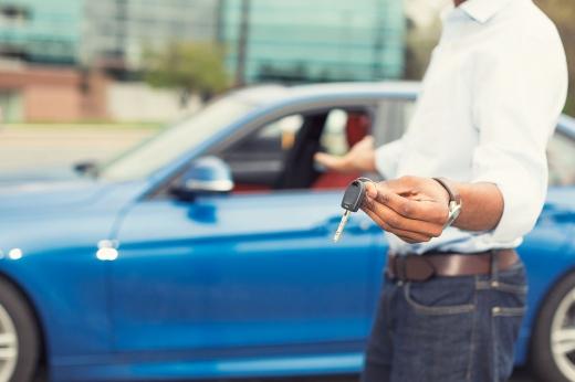Egy férfi ad felén egy slusszkulcsot és mutat egy kék autóra.