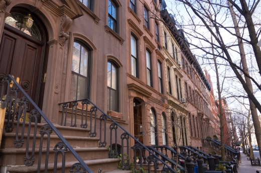 Barnás színű társasházak sora, lépcsővel és kovácsoltvas korláttal, az utcáról fotózva.