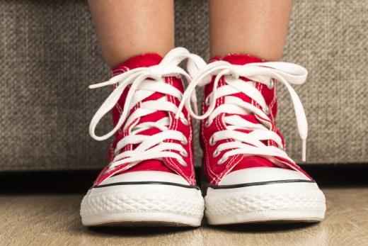 Egy gyerek láb amin piros cipő, fehér fűzővel van.