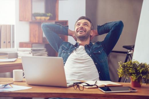 Egy férfi, kezét a tarkójára téve, felfelé nézve mosolyog az íróasztalánál a laptopja elött.