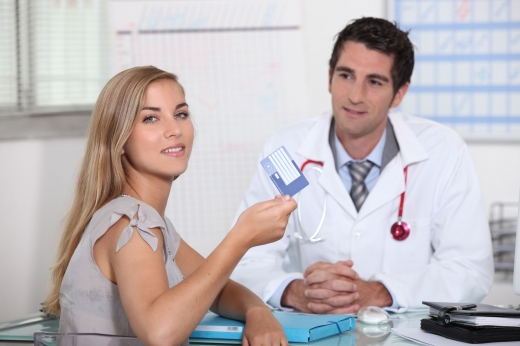 Egy fiatal lány az orvos előtt, felénk fordulva mutatja az Európai Egészségbiztosítási Kártyáját.