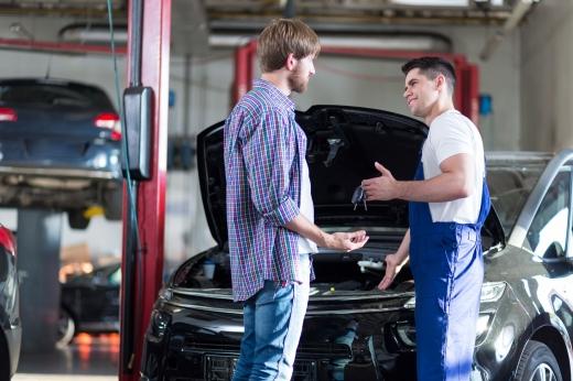 Az autószerelő átadja a tulajdonosnak az autó kulcsait az szerelőműhelyben a karbantartás után.