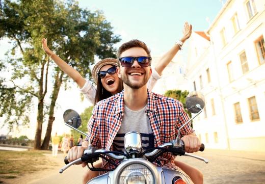 Egy fiatal férfi és lány vidáman jönnek szembe motorral.