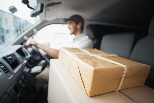 Egy futár az autóban jobb oldalon vezet, bal oldalon több csomag az ülésen.