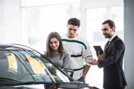 Az autókereskedő mutatja a fiatal párnak az autóját.