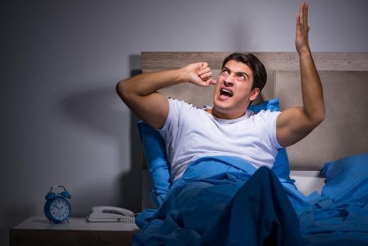 Egy férfi az ágyban bosszankodva befogja a fülét.