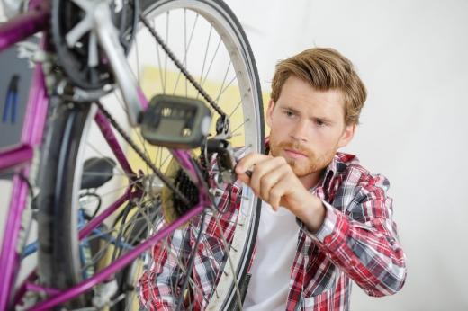 Egy férfi csavarkulccsal a bicikli hátsó kerekét szereli.