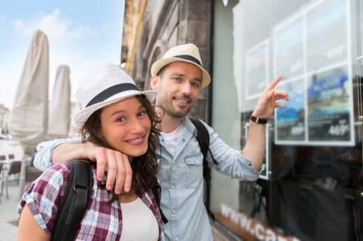 Egy fiatal pár mosolyog nézi az utazási iroda kirakatában lévő hirdetéseket.