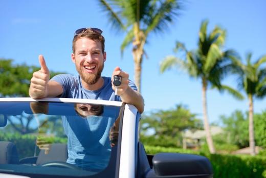 Egy férti kocsikulccsal a kezében, oké jelet mutat az ujjával és vidáman néz ki egy cabrióból a pálmafák között.