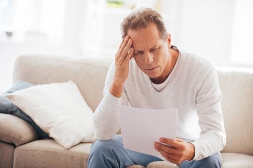Középkorú férfi gondterhelten olvas egy levelet, amiben az állhat hogy tartozást örökölt.