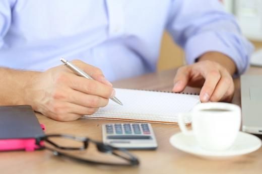 Egy férfi egy papírra ír, az asztalon szemüveg és kávé.