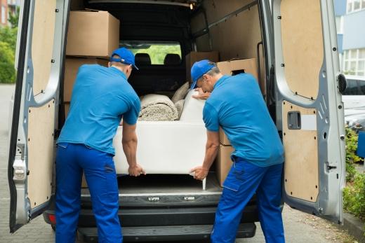 Két kék ruhás férfi egy kisteherautóban bútorokat pakol.