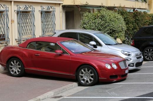 Két drága autó a járdán parkol.