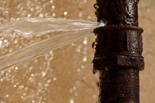 Egy vízcsőből spriccel a víz.