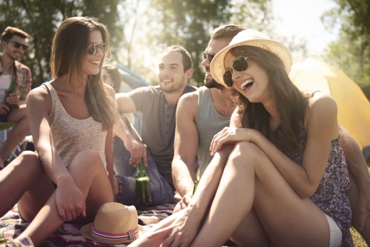 Fiatalok egy fesztiválon, pléden ülve vidámak.