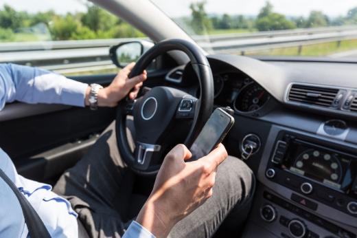 Egy férfi vezetés közben a telefonját nyomkodja.