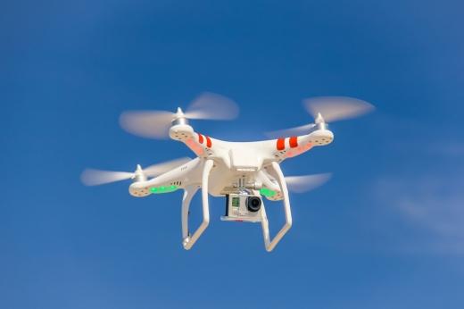 Egy fehér drón repül a kék ég előtt.
