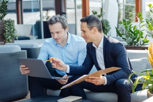 Egy férfi mappával a kezében mutat egy másik férfi laptopjára.