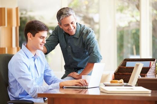 A fiú az asztalnál laptopot használ, az apja az asztalon ülve megdicséri.