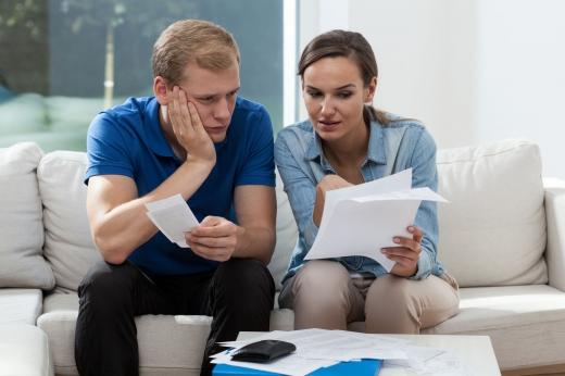 Egy fiatal pár gondterhelten nézik a számláikat.