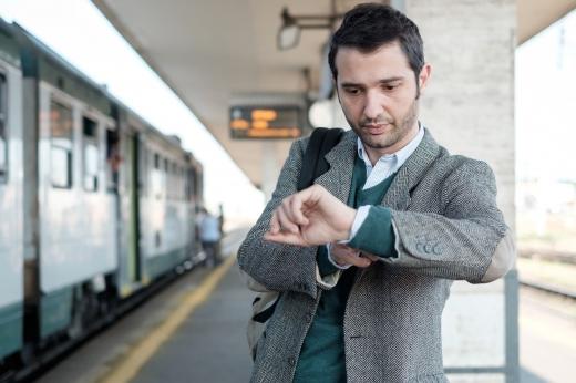 Egy férfi a vasútállomáson, idegesen nézi az óráját.