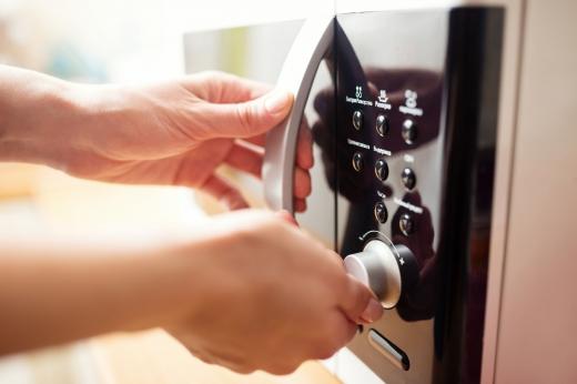 Egy kéz a mikrohullámú sütőt állítja be.