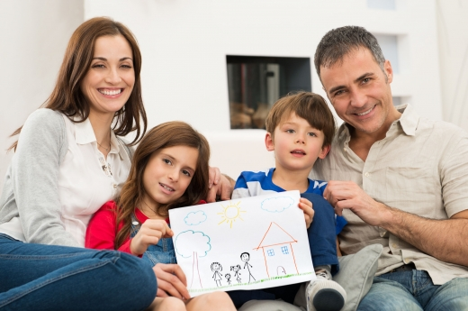 Egy család két gyerekkel egy rajzot mutat felénk.