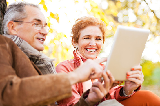 Egy középkorú házaspár ül egy parkon egy padon és együtt olvas. Ősz van, sárga falombok a háttérben.