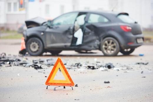 A háttérben egy törött autó, elől egy alakadásjelző háromszög.