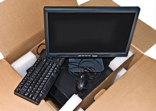 Egy kartondobozban egy számítógép, monitor, egér és billentyűzet.