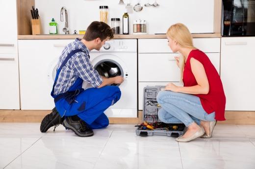 Egy szőke nő és egy mosógépszerelő férfi guggol a hibás mosógép előtt.