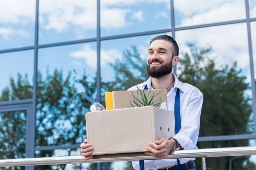 Egy szakállas férfi egy irodaház előtt áll egy kartondobozzal. Kirúgták.