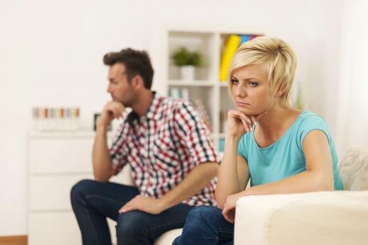 Egy nő és egy férfi egy kanapén mérgesen ellentétes irányba néznek. Haragszanak egymásra.