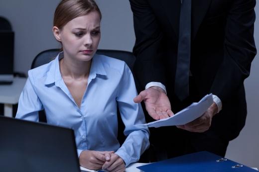 A főnök egy papírt tart egy nő elé és leszidja.