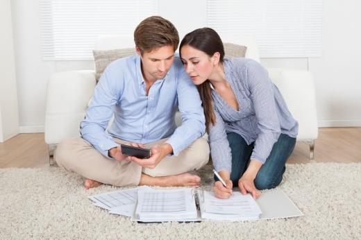 Egy fiatal pár a földön ülve számológéppel számolja a számláikat.