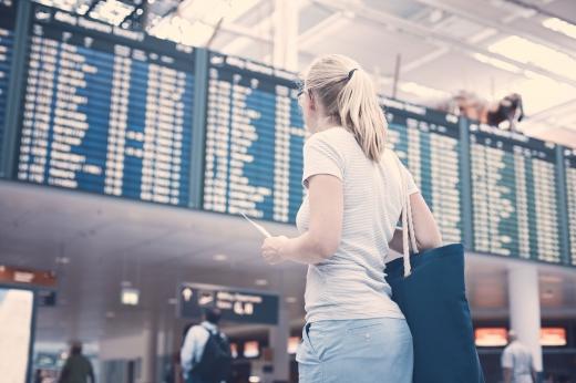 Egy szőke, fehér felsős nő, a reptéren nézi mikor indul a gépe.