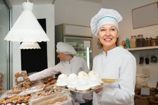 Két fehér ruhás cukrásznő, sütiket pakol a polcokra.