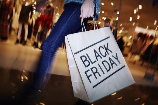 Egy nő deréktól lefelé, egy black friday feliratú szatyrot tart a kezében.