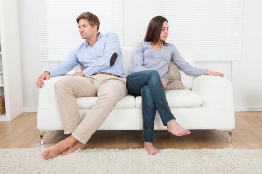 Fiatal pár egy fehér kanapén, ellentétes irányba néznek. Összeveszhettek.