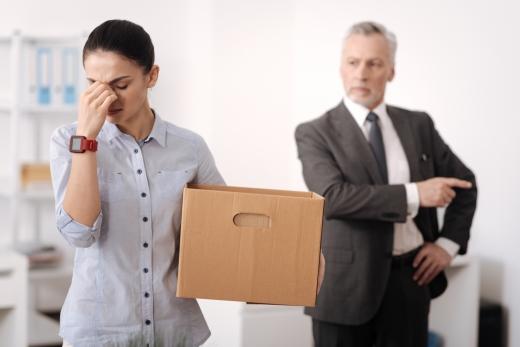 Egy öltönyös férfi szigorúan kirúg egy nőt, akinek papírdoboz van a kezében.